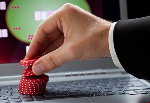 joueur placant des jetons de casino sur un ordinateur portable affichant un casino en ligne