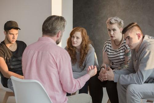 conseiller en addiction parlant avec un groupe de jeunes hommes et femmes