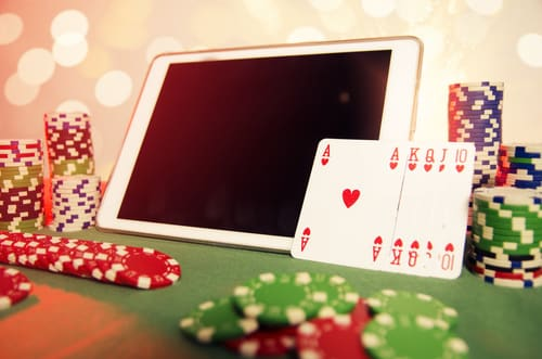 concept de poker en ligne avec une tablette et une pile de jeton de casino